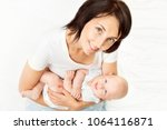 mother and baby  mom holding... | Shutterstock . vector #1064116871