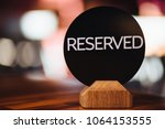 Small photo of Close up of restaurant reserved table sign on table. Inscription denotes booked table in cafeteria. Don`t occupy this place! Table setting. Cafe desk for special occasion