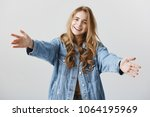 Small photo of Come and give me warm hud. Studio shot of friendly charming young woman in trendy denim jacket, pulling hands towards camera to cuddle friend, smiling happily, showing caring emotions