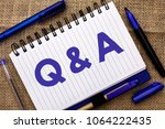 Small photo of Conceptual hand writing showing Q A. Business photo showcasing Ask Frequently Faq Asked Question Help Solving Doubt Query Support written on Notebook Book on jute background Pens next to it.