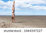 Girl Doing Handstand On A Beach.