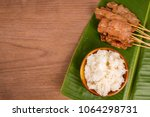 Small photo of grilled pork or moo ping in Thai with sticky rice and Nam Prik Num (Northern Thai Green Chilli Dip) local street food on banana green leaf