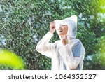 rainy day asian woman wearing a ... | Shutterstock . vector #1064352527