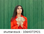 funny casual girl holding money ... | Shutterstock . vector #1064372921
