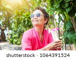 Beautiful mature woman with a cocktail of tropical fruits in her hands. Rest and travel on pension - stock photo