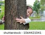 kid hide body behind trunk with ... | Shutterstock . vector #1064421041