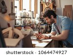 skilled young woodworker... | Shutterstock . vector #1064474927