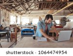 young woodworker with a beard... | Shutterstock . vector #1064474954