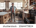 portrait of a young woodworker... | Shutterstock . vector #1064475824