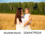 mom and daughter walking in the ... | Shutterstock . vector #1064479034