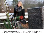 Woman in cemetery sits at a...
