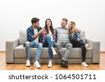 the four happy friends sit on...   Shutterstock . vector #1064501711