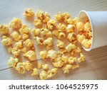 sprinkled popcorn on a wooden... | Shutterstock . vector #1064525975
