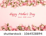 Stock photo mothers day greeting message with small dry roses on pink background flat lay top view happy 1064528894