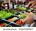 Stock photo fresh salad bar counter with person s hands lifting vegetable into a salad bowl for healthy and 1064530967