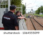 Small photo of KOROLEV, RUSSIA - AUGUST 3, 2016: A policeman talks to a drunken citizen on a railway platform.