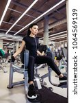 Small photo of Adduction or abductor machine. fit girl exercising her legs in gym