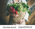 Small photo of Female farmer in linen apron holding basket of fresh garden vegetables and greens in her hands, rustic wooden barn wall at background, horizontal composition. Local market or organic produce concept