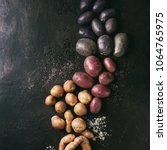 Small photo of Variety of raw uncooked organic potatoes different kind and colors red, yellow, purple with various of salt over dark texture background. Top view, space. Square images