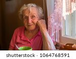 an elderly woman sits at the... | Shutterstock . vector #1064768591