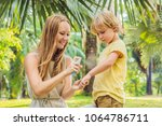 mom and son use mosquito spray... | Shutterstock . vector #1064786711