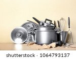Kitchenware prepared for cooking classes on table against light wall