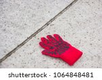 Small photo of A red knitted inger glove lost at a city place with step stones of marble