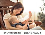 mother holding and feed her... | Shutterstock . vector #1064876375