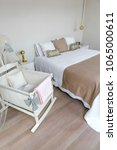 Small photo of Sober and elegant bedroom with double bed and cot with canopy