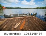 canoe tied to a wooden dock on... | Shutterstock . vector #1065148499