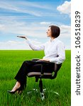beautiful businesswoman sitting on recliner and holding something on her hand - stock photo