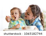 smiling mom feeding baby... | Shutterstock . vector #1065182744
