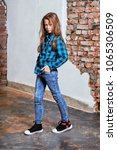 Small photo of Teenager poses for advertising youth clothing,store.Female hipster child modern 9-13 years in bright blue shirt in cage, jeans,sneakers,looks confidently,boldly.Full growth.Youthful fashion style.
