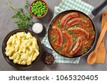 Small photo of delicious juicy fried hot sausages with brown crust in thick onion gravy in a skillet on concrete table with mashed potatoes and green peas in bowls, classic recipe - bungers and mash, view from above