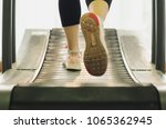 Small photo of Woman runner feet exercising to running on treadmill in gym with warm light, She is jogging, fitness and jog workout wellness concept, selective focus