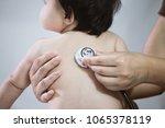 doctor examining asian baby... | Shutterstock . vector #1065378119
