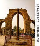 Small photo of New Delhi, India - January 2018: 7 meter iron pillar of in the Kutub Complex is a victory column erected and dedicated to Hindu deity Vishnu in 3rd to 4th century CE by King Chandra