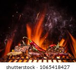 tasty beef steaks on the grill... | Shutterstock . vector #1065418427