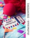 Small photo of a curly red hair wig, a red clown nose and the text happy circus day in a simulated admission ticket made by myself, on a blue rustic wooden surface full of confetti
