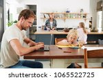 dad and son at kitchen table ... | Shutterstock . vector #1065522725