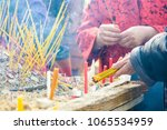 Small photo of Close-up view of the hands of a woman wearing an asian style blouse lighting incense sticks with lighted candles before sticking them into a pile of sand on a wooden table during a buddhist ceremony.