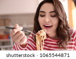 young woman eating tasty pasta... | Shutterstock . vector #1065544871