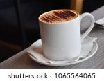 a white mug of hot cappuccino... | Shutterstock . vector #1065564065