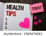 Small photo of Conceptual hand writing showing Health Tips. Business photo showcasing Healthy Suggestions Suggest Information Guidance Tip Idea written on Notebook Book on wooden background Today Heart.