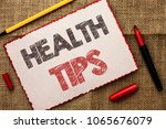 Small photo of Writing note showing Health Tips. Business photo showcasing Healthy Suggestions Suggest Information Guidance Tip Idea written on Cardboard Piece on the jute background Markers next to it.