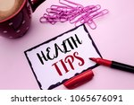 Small photo of Text sign showing Health Tips. Conceptual photo Healthy Suggestions Suggest Information Guidance Tip Idea written on Sticky Note Paper on the plain background Marker Cup Pins next to it.