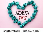 Small photo of Conceptual hand writing showing Health Tips. Business photo text Healthy Suggestions Suggest Information Guidance Tip Idea written on Plain background within Heart Paper Balls.