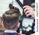 Small photo of Barber is using hairdryer and hairbrush to make a styling to a Caucasian boy.