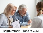 Small photo of Older couple reading contract at meeting with real estate agent considering new home purchase, realtor or bank worker consulting senior family about buying house loan with project plan on laptop