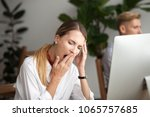 bored businesswoman yawning at... | Shutterstock . vector #1065757685